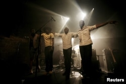 FILE - Malian band Songhoy Blues members, left to right, Nathanael Dembele, Garba Toure, Aliou Toure and Oumar Toure, react at the end of their concert at Village Underground in London, Britain, May 28, 2015.