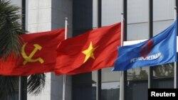 Lá cờ truyền thống của PetroVietnam (phải) tung bay bên cạnh quốc kỳ và cờ của Đảng Cộng sản, ảnh chụp trước trụ sở chính của PetroVietnam ngày 11/1/2016. REUTERS/Kham