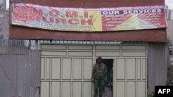 Солдат кенийских военизированных формирований охраняет вход в церковь, где прогремел взрыв. Найроби, Кения