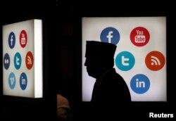 Seorang delegasi pertemuan Bank Pembangunan Islam (IDB) berjalan melintasi logo-logo platform media sosial di Jakarta Convention Center di Jakarta, 16 Mei 2016.(Foto: Reuters)