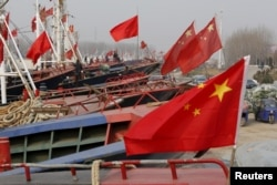 FILE - China's national flags are seen on fishing boats preparing for spring fishing in Lianyungang, Jiangsu Province, China, March 26, 2016.