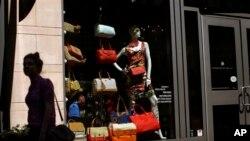 2013年4月10日,一位女士走过巴尔的摩一家零售店的橱窗。美国商务部6月26日公布的报告显示,1-3月第一季度的美国消费者的消费水平低于预期。