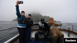 """Holidaymakers take a selfie, along with Star Wars fans dressed in costume as Darth Vader and Chewbacca, on a boat trip to Skellig Island during the inaugural """"May The 4th Be With You"""" festival in the County Kerry village of Portmagee, Ireland, May 4, 2018"""