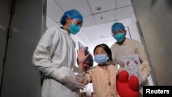 A girl, who was previously infected with the H7N9 bird flu virus, waves as she is being transferred to a public ward from the ICU at Ditan hospital in Beijing, Apr. 15, 2013.