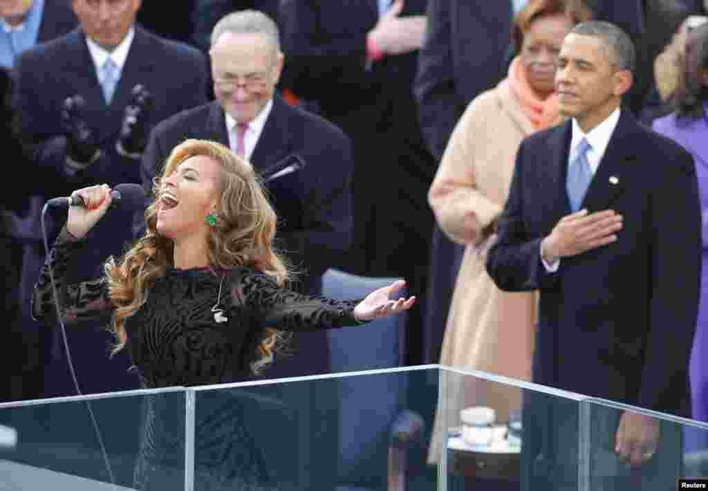 Trên khán đài, ca sĩ Beyonce hát quốc ca, phía sau là Tổng thống Obama và Thượng nghị sĩ Charles Schumer của New York (đeo kính) tại lễ nhậm chức nhiệm kỳ hai của Tổng thống Obama. (Reuters)