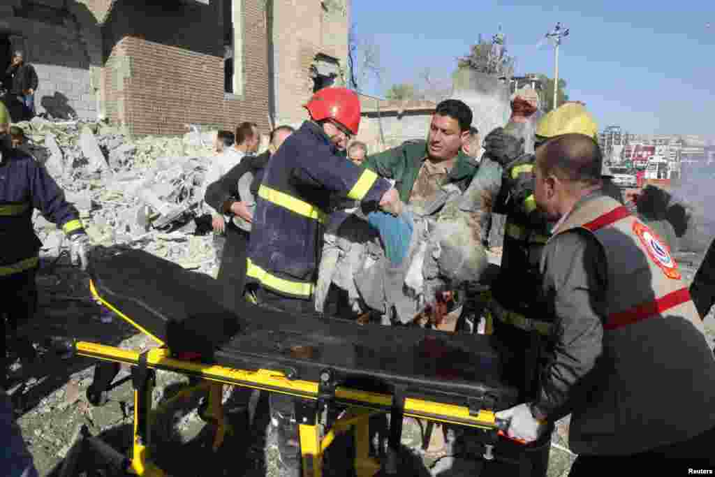 Medical personnel carry a victim to a stretcher at the site of a suicide bomb attack in Kirkuk, Iraq, February 3, 2013.