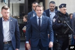 French centrist presidential candidate Emmanuel Macron, center, leaves his apartment, in Paris, April 24, 2017.