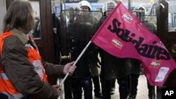 A demonstrator holds a trade union flag as French riot police officers secure the area at the Bordeaux train station, southwest France, Friday Oct. 22, 2010, during a demonstration against President Nicolas Sarkozy's bid to raise the retirement age to 62.