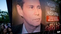 Beberapa perempuan berdiri di samping poster mendiang Jaksa Penuntut Alberto Nisman dalam peringatan satu tahun kematiannya di Buenos Aires, Argentina, 18 Januari 2016.