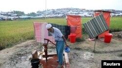 Seoran pengungsi Rohingya memompa air untuk minum tidak jauh dari lokasi jamban di Cox's Bazar, Bangladesh.