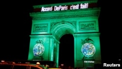 "FILE - The Arc de Triomphe is illuminated in green with the words ""Paris Agreement is Done,"" to celebrate the Paris U.N. COP21 Climate Change agreement in Paris, France, Nov. 4, 2016."