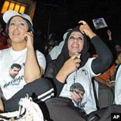 "In this 2004 file photo, Kuwaiti women sitting in front of a screen use mobiles to vote for their national Bashar Al-Shatti who was competing for title of pan Arab entertainment program ""Star Academy"""