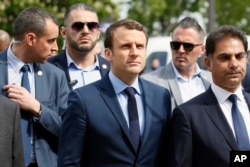 French centrist presidential candidate Emmanuel Macron, center, next to Mourad Franck Papazian, left, co-president of France's Armenian Organizations Coordination Council (CCAF), right, arrives for a ceremony marking 102nd anniversary of the slaying of Armenians by Ottoman Turks in a brief ceremony in Paris, April 24, 2017.