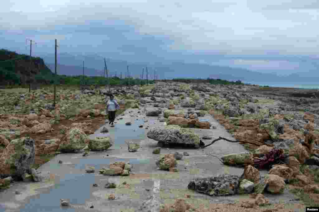 A woman walks on a highway blocked by rocks after the passage of hurricane Matthew on the coast of Guantanamo province, Cuba.