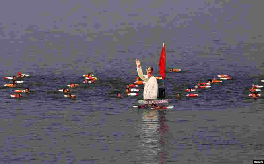 Para peserta lomba renang berenang dengan gambar tokoh China mendiang Mao Zedong si sungai Hanjiang, cabang sungai Yangtze, di Xiangyang, China.
