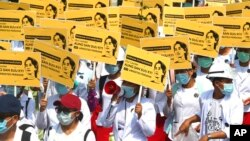 Medicals students display images of deposed Myanmar leader Aung San Suu Kyi during a street march in Mandalay, Myanmar. By midday, security forces had blocked the main road in downtown Mandalay to prevent the protesters from gathering.