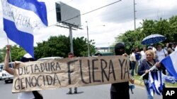"Banner: ""Genocidal Dictatorship Out Now"" during a demonstration demanding the resignation of President Daniel Ortega and the release of all political prisoners, Managua, Nicaragua. (July 30, 2018.)"
