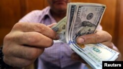 An employee counts money in a foreign exchange office in central Cairo, Egypt, November 3, 2016. The wide gap between Egypt's official and unofficial dollar rates has led people to insist on receiving their money in foreign currency from the bank and the