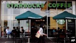 A Muslim woman walks past a Starbucks coffee shop in Rawang outside Kuala Lumpur, Malaysia, July 6, 2017.