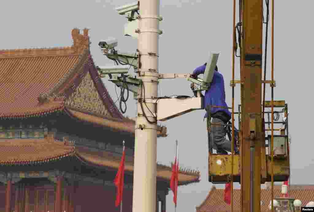 A man installs a security camera at the Tiananmen Square in Beijing, Oct. 31, 2013.