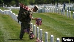 2021年5月27日一名軍人在美國維吉尼亞州阿靈頓國家公墓放置國旗。