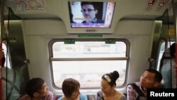 Los pasajeros del tren en Hong Kong escuchan noticias de que Snowden dijo al periodista Greenwald del diario The Guardia que no facilitó información a China ni a Rusia.