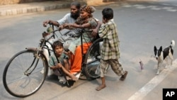A beggar family commutes on a handcycle with their pet dog following on a leash in New Delhi, India, Saturday, Oct. 26, 2013.