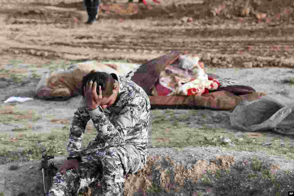 An Iraqi policeman pulls himself together as he is surrounded by bodies at the site of a mass grave containing some two dozen people, many of them children, in an area recently re-taken from Islamic State militants in Mosul, March 15, 2017.