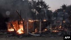 Ngôi nhà trong ngôi làng phía Thái Lan bị cháy trong trận giao tranh giữa binh sĩ Thái và Kampuchea