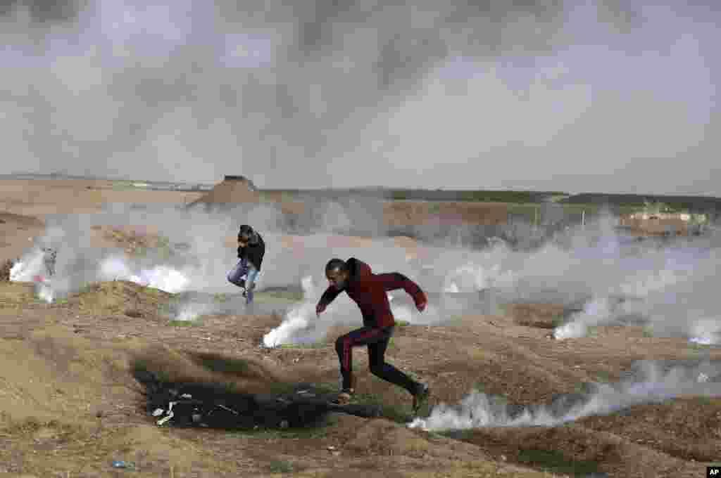 가자지구와 이스라엘 간 보안장벽 인근에서 팔레스타인 시위대가 이스라엘군이 발포한 최루가스를 피해 달아나고 있다.