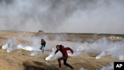 Palestinian protesters run for cover from teargas fired by Israeli troops during a protest at the Gaza Strip's border with Israel, Friday, April 13, 2018. (AP Photo/ Khalil Hamra)