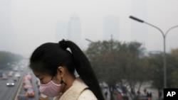 Una mujer usando una máscara para protegerse de la contaminación en Beijing.