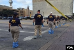 FBI investigators search for evidence in Thursday's sniper attack on police officers in downtown Dallas, Texas, July 9, 2016. (G. Tobias/VOA News)