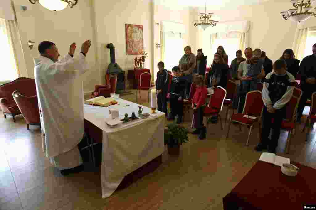 Priest Cezary Korzec conducts a Holy Mass in a chapel in his house in the village of Rosow, Germany, located near the Polish border, April 7, 2013.