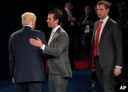 FILE - Donald Trump talks to his sons Donald Trump Jr. and Eric Trump after the second presidential debate, Oct. 9, 2016.