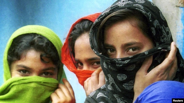 FILE - Young girls in Bangladesh cover their faces with clothes, apparently trying to hide their age, March 5, 2000.