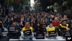The students of Ankara University hold the placards with the names of those killed in Saturday's deadly explosions during a sit-in protest in Ankara, Turkey, Oct. 13, 2015.