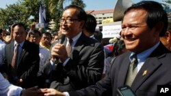 Opposition leader of Cambodia National Rescue Party Sam Rainsy, center, delivers a speech next to his Deputy President Kem Sokha, right, during a gathering to mark Human Rights Day, in front of National Assembly, in Phnom Penh, Cambodia, file photo.