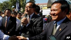 Opposition leader of Cambodia National Rescue Party Sam Rainsy, center, delivers a speech next to his Deputy President Kem Sokha, right, during a gathering to mark Human Rights Day, in front of National Assembly, in Phnom Penh, Cambodia, Wednesday, Dec. 1