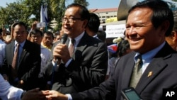 Opposition leader of Cambodia National Rescue Party Sam Rainsy, center, delivers a speech next to his Deputy President Kem Sokha, right, during a gathering to mark Human Rights Day, in front of National Assembly, in Phnom Penh, Cambodia, Wednesday, Dec. 10, 2014. (AP Photo/Heng Sinith)