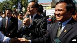 Opposition leader of Cambodia National Rescue Party Sam Rainsy, center, delivers a speech next to his Deputy President Kem Sokha, right, during a gathering to mark Human Rights Day, in front of National Assembly, file photo.