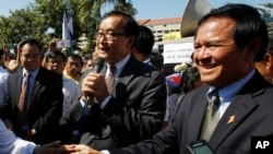 Opposition leader of Cambodia National Rescue Party Sam Rainsy, center, delivers a speech next to his Deputy President Kem Sokha, right, during a gathering to mark Human Rights Day, in front of National Assembly, in Phnom Penh, Cambodia, Wednesday, Dec. 10, 2014. (AP Photo/Heng Sinith