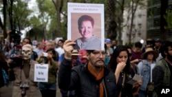 Seorang pria mengangkat foto wartawan Meksiko, Miroslava Breach, yang ditembak mati di negara bagian Chihuahua hari Kamis, selama pawai di Mexico City, 25 Maret 2017 (foto: AP Photo/Eduardo Verdugo)