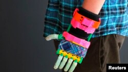 Prosthetic limbs have come a long way. Here a 12-year-old boy shows off his new, colorful, 3-D printed prosthetic hand at the new MakerBot store in Boston, Massachusetts. (Nov. 2013)