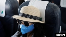 A woman wears a protective mask onboard during a flight of Bamboo Airways from Da Nang to Hanoi, Vietnam March 7, 2020. REUTERS/Kham