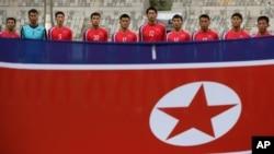 지난 18일 인천 아시안게임 남자축구 F조 1차전 파키스탄과의 경기에 출전한 북한 선수단이 인공기 앞에 서 있다.