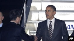 President Barack Obama is welcomed by Japanese Foreign Minister Seiji Maehara, left, upon arrival at Haneda international airport in Tokyo Friday, Nov. 12, 2010. Obama is visiting Japan to attend meetings of the APEC forum held in Yokohama this weekend. (