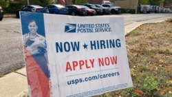 A now hiring sign stands in the parking lot of the University Hills branch of the United States Postal Service, Oct. 12, 2021, in southeast Denver.