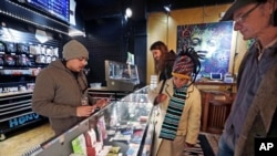 FILE - Cannabis consultant Juan Aguilar, left, assists customers Bill, right, and Nize Nylen and their son Russell shop for edible marijuana products in the Herban Legends pot shop, Thursday, Jan. 4, 2018, in Seattle. (AP Photo/Elaine Thompson)