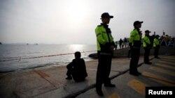 Anggota keluarga penumpang kapal Korea Selatan yang tenggelam menapat laut dari pelabuhan tempat para keluarga penumpang berkumpul di Jindo (20/4). (Reuters/Kim Hong-Ji)